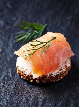 Smoked salmon canap? with cream cheese on black stone background. Close up.