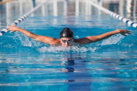 Photo pour dynamic swimmer in cap glasses in the pool - image libre de droit