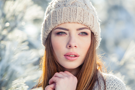 Beautiful winter portrait of young woman in the winter snowy scenery.の写真素材