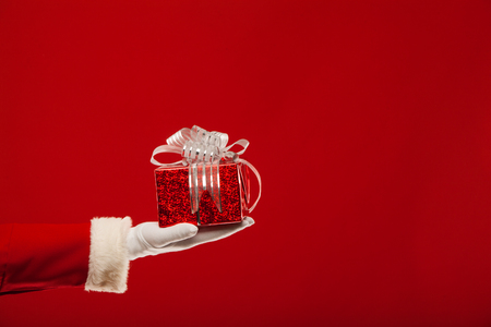 Photo of Santa Claus gloved hand with red giftbox, on a red background