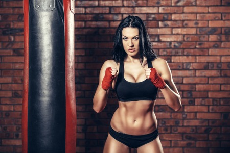 Young beautiful sexy boxer woman with red boxing bandage on hands.