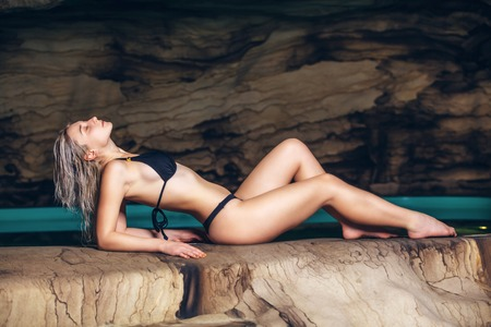 Photo for Happy young woman in swimsuit enjoying sitting in cave near the lake. - Royalty Free Image