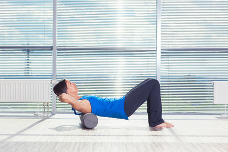 Photo pour fitness, sport, training and lifestyle concept - woman doing pilates on the floor with foam roller. - image libre de droit