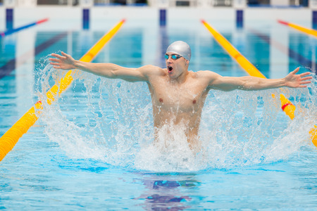 dynamic and fit swimmer in cap breathing performing the jumping out of the water, the concept of victory, freedom, happiness, healthy lifestyle