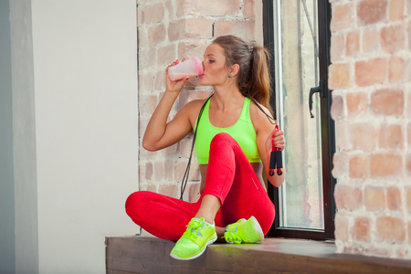 beautiful young girl is drinking a fitness smoothie.の写真素材