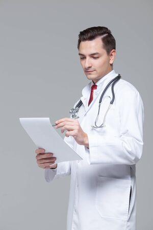Photo pour Portrait of young doctor in white uniform with stethoscope holding folder - image libre de droit