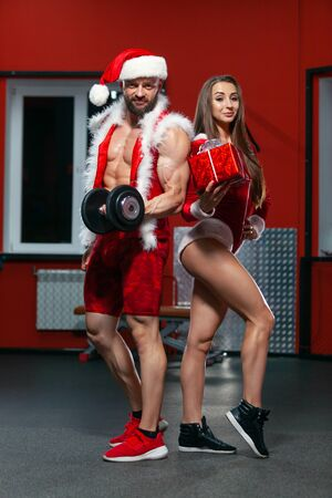 Photo for Christmas. Handsome muscular man in Santa Claus suit with dumbbells and fitness woman in red suit with gift . GYM. - Royalty Free Image