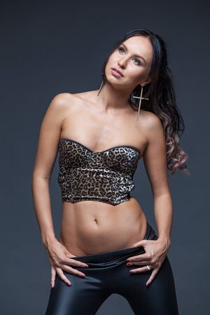 Photo for Beautiful, sexy and sensual brunette model girl with bright makeup in a trendy leopard print top and black leather pants seductively looking at the camera and posing at dark background - Royalty Free Image