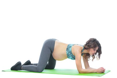 Foto de Beautiful pregnant woman workout. Doing fitness on last months of pregnancy. Yoga positions. Motherhood, pregnancy, yoga concept. Isolated white background. - Imagen libre de derechos