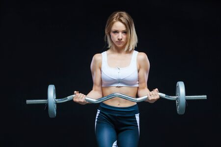 Photo for Close-up portrait of a fitness Muscular young girl posing with curly barbell at the gym isolated on a black background - Royalty Free Image