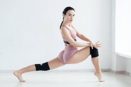 Photo pour Attractive young woman does a stretching exercise on the floor looking at camera - image libre de droit