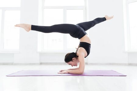 Photo for Young woman practicing yoga, standing in handstand exercise, working out, wearing black sportswear, on the floor near window - Royalty Free Image