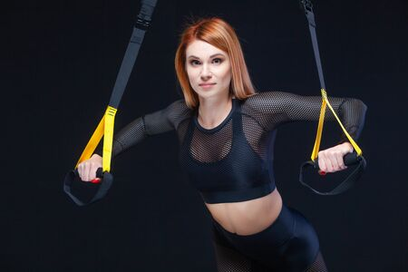 Beautiful fitness woman training with trx fitness straps in sexy sportswear isolated on black background