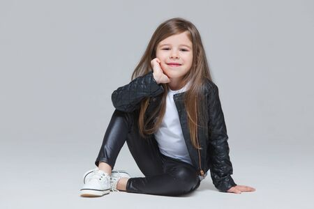 Foto de Baby girl with long hair in black leather jacket and leggings is sitting in the studio on grey background - Imagen libre de derechos