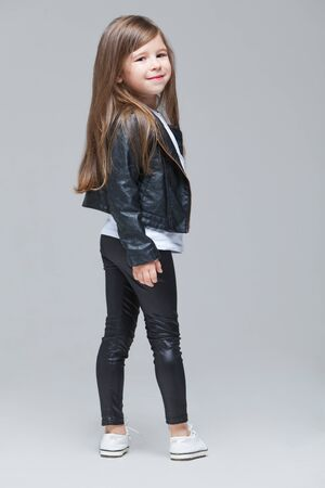 Foto de Baby girl with long hair in black leather jacket and leggings is standing in the studio on grey background - Imagen libre de derechos