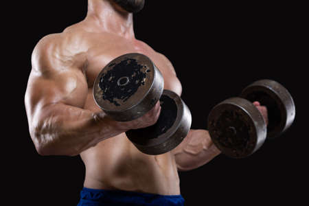 Photo pour Close up of muscular sportsman lifting heavy dumbbells showing his strong biceps isolated on black backgrounds - image libre de droit
