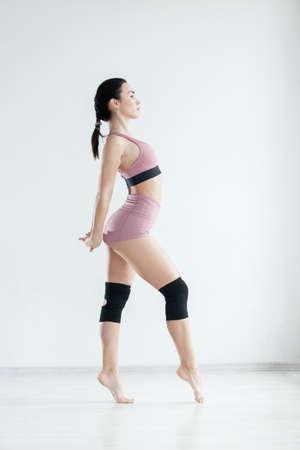 Foto für Sporty slim girl in pink sportswear stands straight with one raised hand warming up before workout - Lizenzfreies Bild