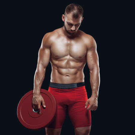 Photo for Photo of athletic young man with naked torso and good physique with heavy weight disc on black background - Royalty Free Image