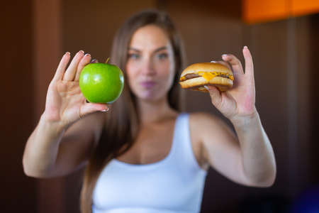 Photo for Young attractive girl is making choice between healthy and harmful food holding a green apple and a burger in her hands. Concept of proper nutrition, healthy food, fast food - Royalty Free Image