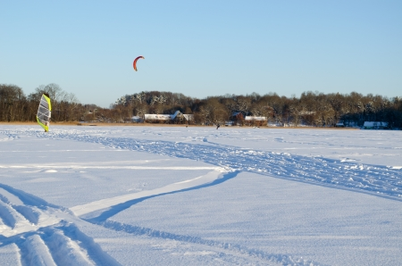 people kiteboarding and ice sailing on frozen lake in amazing cold winter day modern recreation hobby