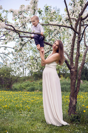 pregnant girl with long hair wearing a long white dress standing in the street near the Apple trees with white flowers