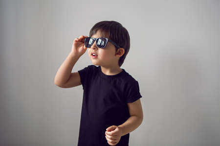 Photo for boy in a black t-shirt stands at home against the background of a white room in sunglasses ,during quarantine and thinks about traveling to countries - Royalty Free Image