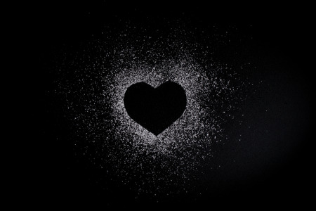 Photo pour Heart shape made of icing sugar on total black background with copyspase. Concept of Valentine's day and sweet romantic love - image libre de droit