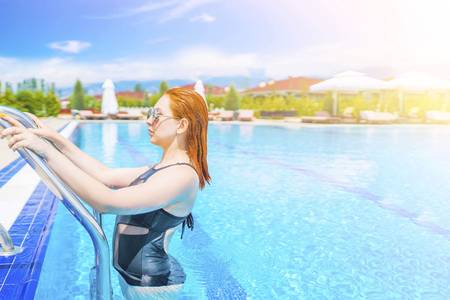 Woman getting out of the blue water in the pool. Young female resting in swimming pool at spa resort. Luxury relaxing concept.