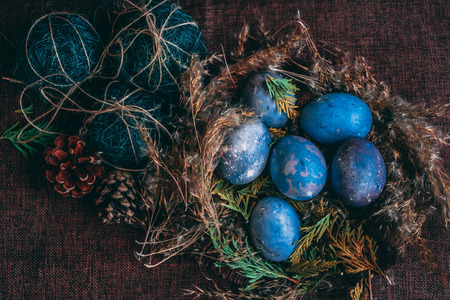 Photo for space galactic Easter eggs in nest next to cone and green filler - Royalty Free Image