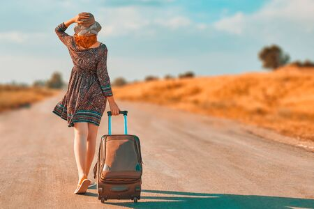 Photo pour Pretty woman in summer dress and hat hitchhiking with suitcase. Girl walking on the road with Luggage at fall. Journey concept - image libre de droit