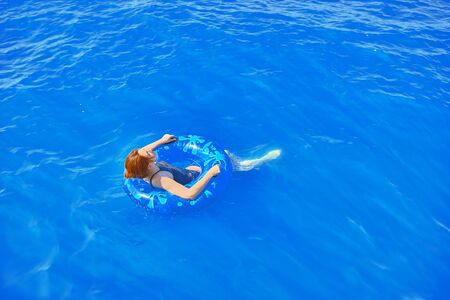 Photo pour Amazing young woman with inflatable ring relaxing in blue raging ocean - image libre de droit