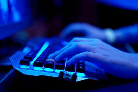 Photo pour Gaming Keyboard. Closeup of hands on neon lit keyboard. Streaming online games on internet. - image libre de droit