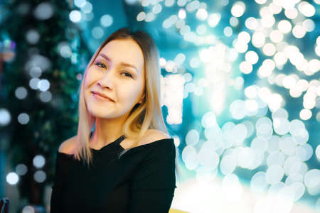 Foto de Portrait of awesome woman against background of bright lights. Female posing at camera in lounge bar. Copy space for text or advertisement. Night holiday party. - Imagen libre de derechos