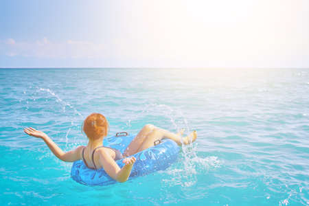 Photo pour Red-haired girl splashes water. Beautiful young woman resting on an inflatable ring in the sea water. Summer holidays. Cheerful woman with a swimming balloon. - image libre de droit