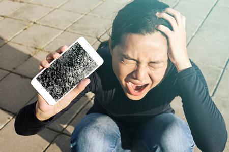 Photo pour Screaming woman  holding a screen crack the smartphone outdoor. - image libre de droit
