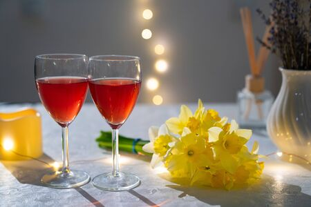 Photo pour two glasses with red wine on the table with a bouquet of yellow daffodils in the evening - image libre de droit