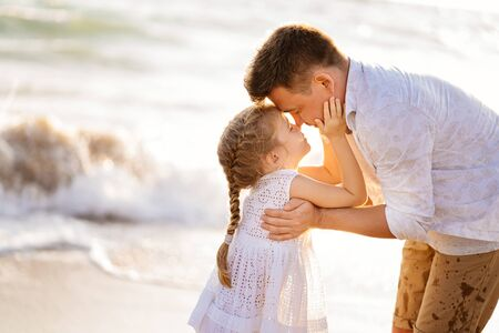 Photo for kiss. dad with daughter walking along the sea-shore in windy weather. fun family games with the kids. the trip into a vacation. - Royalty Free Image