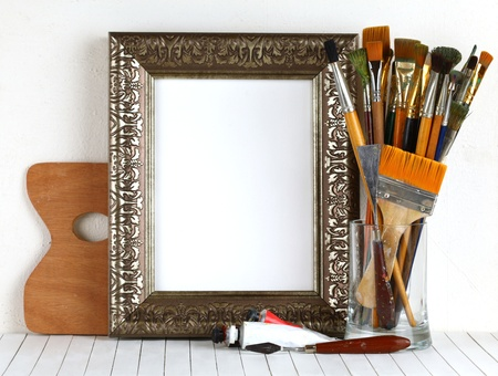 Picture gold frame with a palette and paintbrushes