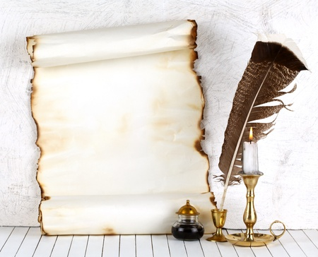 Old paper with a candle and a quill pen.On a white background.