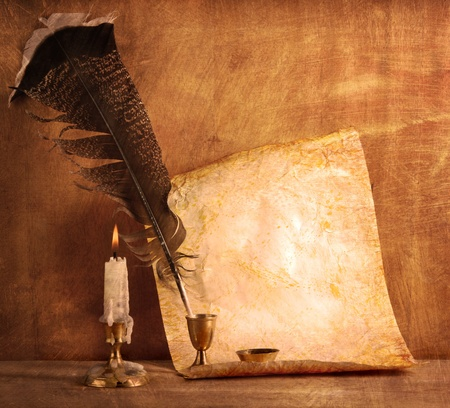 Old paper with a candle and a quill pen