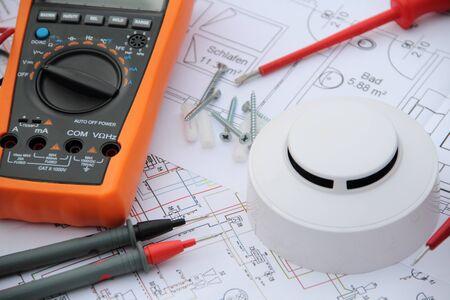 Photo pour Smoke detector with a screwdriver and a measuring device on a circuit diagram - image libre de droit