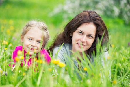 Photo for Mother and daughter lying on green summer grass with blooming yellow flowers - Royalty Free Image