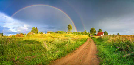 Photo for Rainbow over stormy sky. Rural landscape with rainbow over dark stormy sky in a countryside at summer evening. - Royalty Free Image