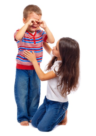 Girl calming down her little crying brother, isolated on white