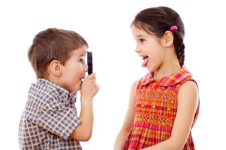 Boy looks at girl with a magnifying glass, isolated on white