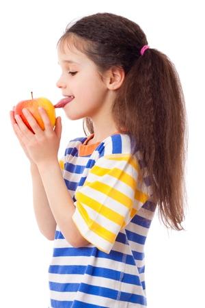 Dreaming girl tasting the apple, isolated on white