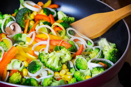 frying vegetables in pan with spatula close up