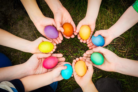 Photo for Colorful easter eggs in child hands after egg-hunt - Royalty Free Image