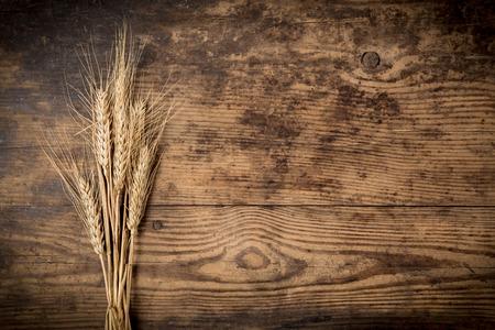 Sheaf of wheat ears on dark wooden background