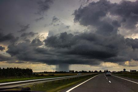 Photo pour Storm clouds with rain over the road. - image libre de droit